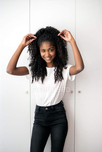 Retrato de una joven adolescente negra mirando a la cámara en un fondo blanco - foto de stock