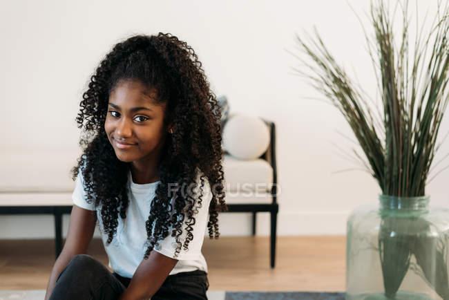 Молодая чернокожая девочка-подросток, сидящая в кресле — стоковое фото