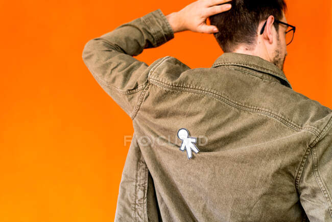 Back view of guy with paper silhouette for April fools day on jean jacket on orange background — Stock Photo