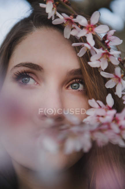 Face of young lady with blue eyes near branch of blooming fruit tree — Stock Photo