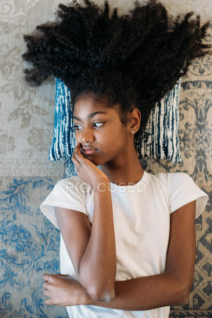 Young black teenage girl lying down in a rug — Stock Photo