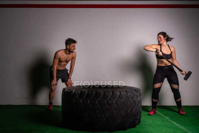 Shirtless guy standing near athletic young concentrated lady in sportswear with hammer hitting on big tire in gym - foto de stock