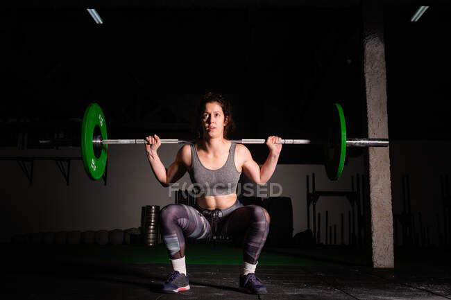 Спортивна молода сконцентрована жінка у спортивній манері висячи над головою у спортзалі. — стокове фото
