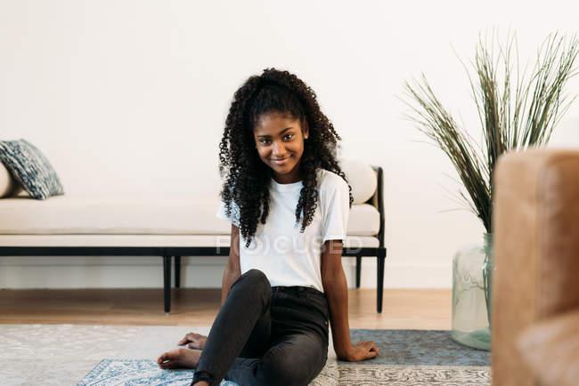Junges schwarzes Teenager-Mädchen sitzt auf einem Teppich — Stockfoto