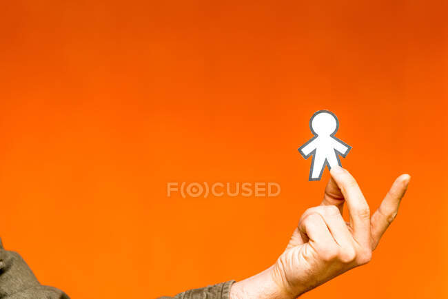 Happy guy showing paper silhouette for April fools day on orange blurred background — Foto stock