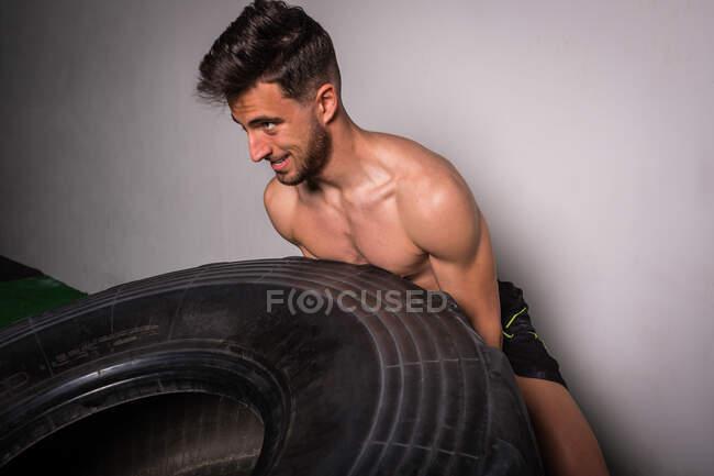 Atlético jovem shirtless cara ter competição de lançando grandes pneus no ginásio — Fotografia de Stock