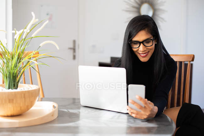 Businesswoman working from home on her computer and speaking on the mobile phone — Stock Photo