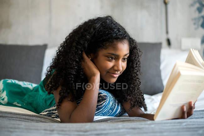 Счастливая чернокожая девочка-подросток на кровати читает книгу — стоковое фото