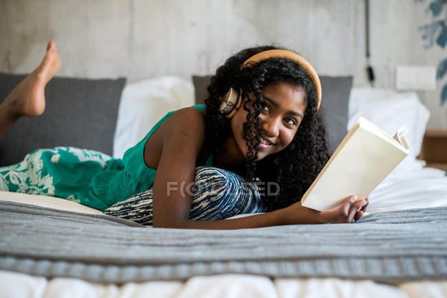 Счастливая чернокожая девочка-подросток в наушниках на кровати читает книгу — стоковое фото