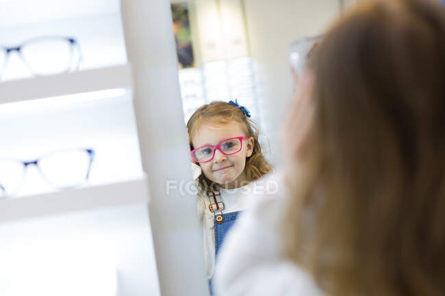 Cute young girl trying on glasses in an eyewear store — Fotografia de Stock