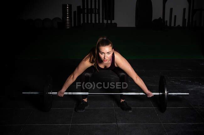 Атлетичная молодая сконцентрированная леди в спортивной одежде, поднимающая штангу над головой в спортзале — стоковое фото