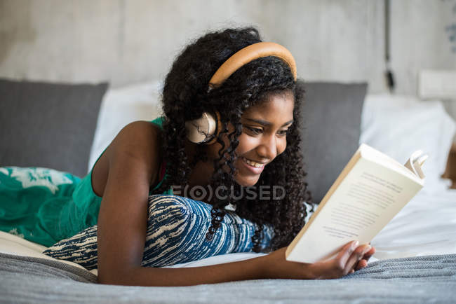Happy black teenage girl with headphones on bed reading a book — Stock Photo