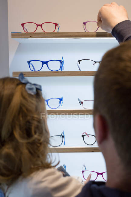 Cute young girl trying on glasses in an eyewear store — стокове фото