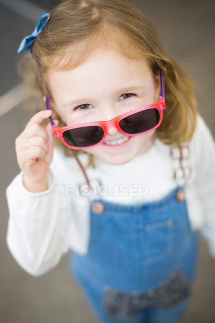 Cute young girl trying on glasses in an eyewear store — Stockfoto