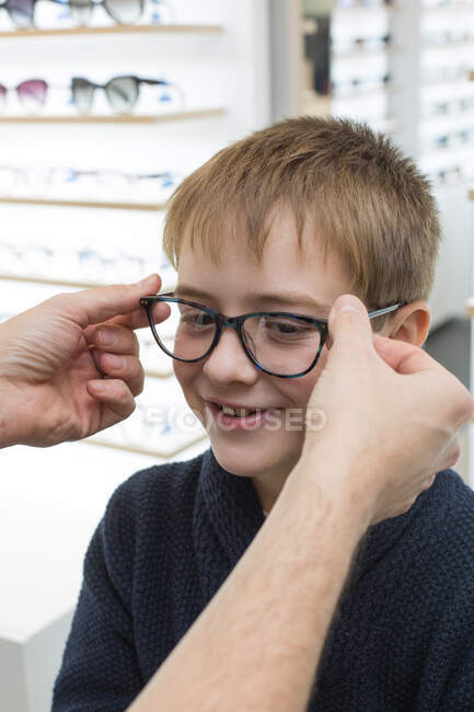 Cute young boy trying on glasses in an eyewear store — Stock Photo