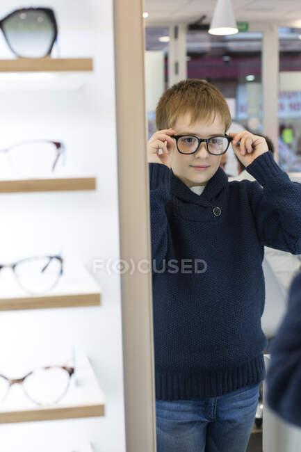 Милый мальчик примеряет очки в магазине очков. — стоковое фото