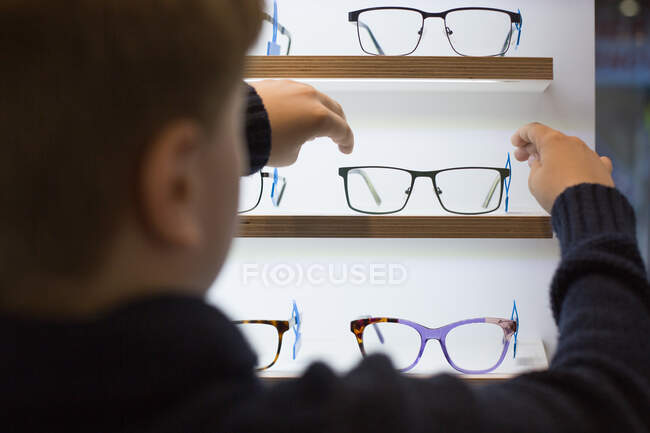 Cute young boy trying on glasses in an eyewear store — стокове фото