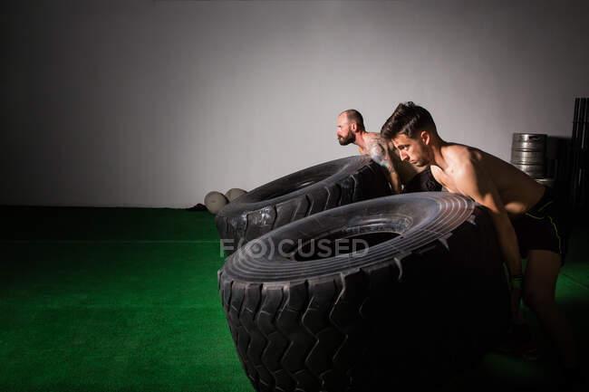 Вид сбоку на атлетичных молодых парней без рубашки, которые соревнуются за прокачку больших шин в спортзале — стоковое фото