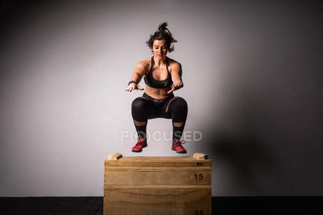 Athletic young lady in sportswear with reached out hands jumping on wooden box in gym on grey background — Stock Photo