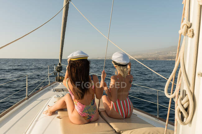 Side view of beautiful young females in sunglasses and captain hats sitting on deck of expensive boat floating on water in sunny day — Stock Photo
