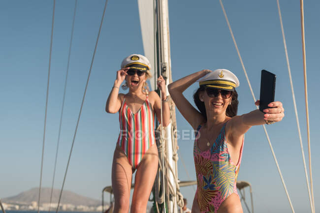 Beautiful young females in sunglasses and captain hats taking selfie on mobile phone and sitting on deck of expensive boat floating on water in sunny day — Photo de stock