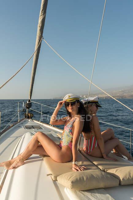 Вид сбоку на красивых молодых женщин в солнцезащитных очках и капитанских шляпах, сидящих на палубе дорогой лодки, плавающей на воде в солнечный день — стоковое фото