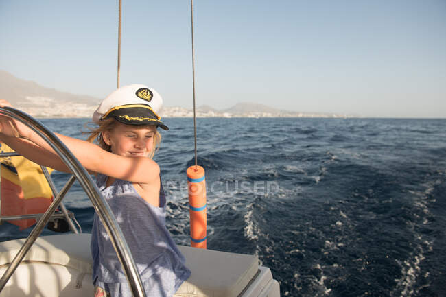 Positive kid in captain hat floating on expensive boat on sea in sunny day — Stockfoto