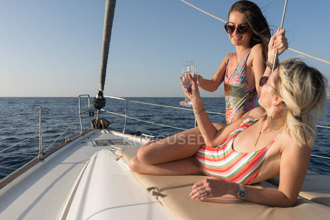 Crop young females in swimsuits with glasses of champagne and resting on deck of expensive boat floating on water in sunny day — Stock Photo