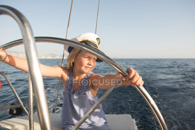 Positive kid in captain hat floating on expensive boat on sea in sunny day — Stock Photo