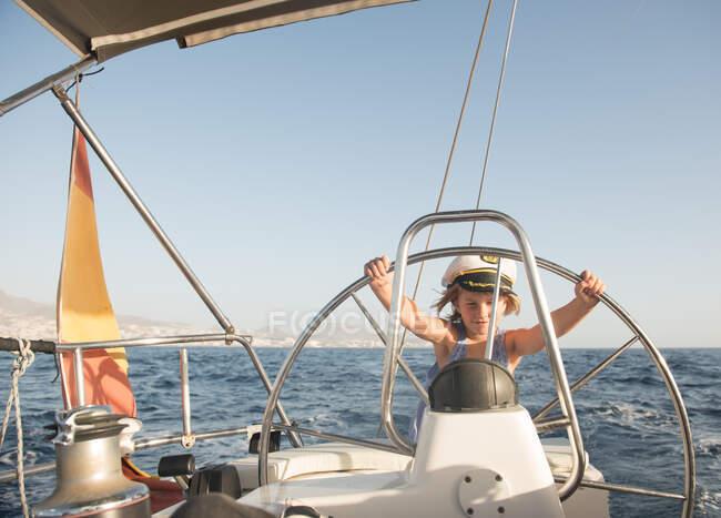 Позитивный ребенок в капитанской шляпе, плавающий на дорогой лодке по морю в солнечный день — стоковое фото