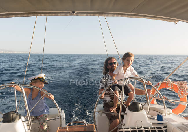 Happy father with children floating on expensive boat on sea and blue sky in sunny day — Stock Photo