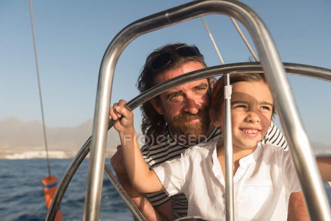 Buon padre con bambini che galleggiano su costose barche in mare e cielo blu nella giornata di sole — Foto stock