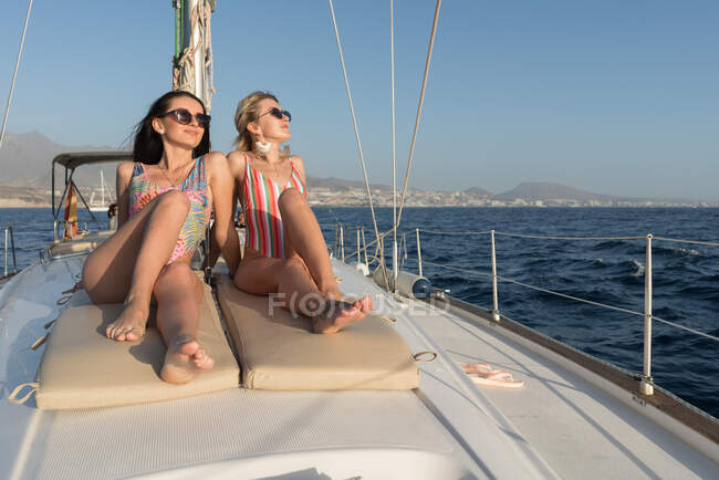 Beautiful young females in sunglasses and captain hats on side deck of expensive boat floating on water in sunny day — Stock Photo