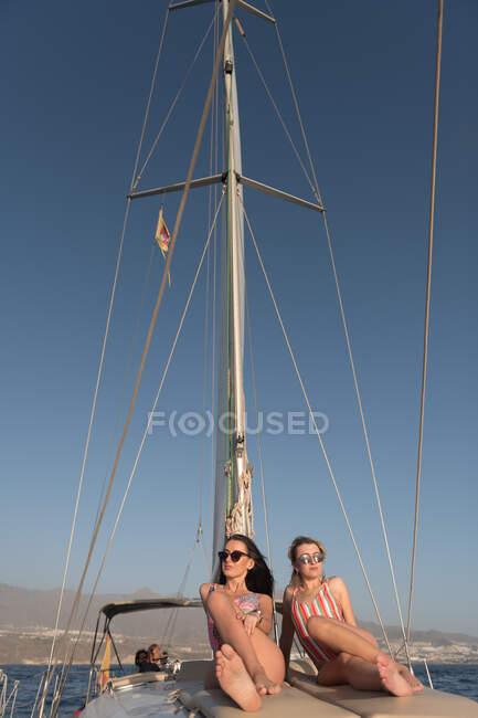 Красивые молодые женщины в солнечных очках и капитанские шляпы на боковой палубе дорогой лодки, плавающей на воде в солнечный день — стоковое фото