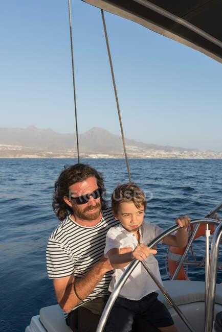 Glücklicher Vater mit Kindern auf teurem Boot auf dem Meer und blauem Himmel bei sonnigem Tag — Stockfoto