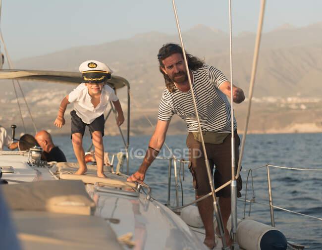 Padre e figlio in cappello da capitano galleggiano su una costosa barca in mare nella giornata di sole — Foto stock