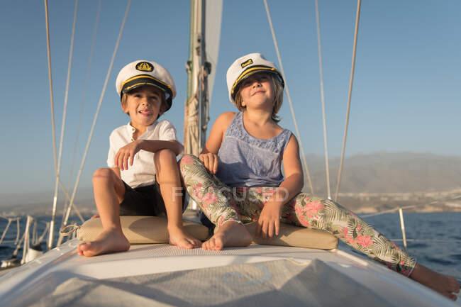 Bambini positivi con cappelli da capitano seduti sul ponte di barca costosa che galleggia sull'acqua nella giornata di sole — Foto stock