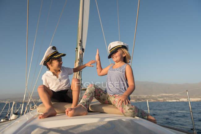 Позитивные дети в капитанских шляпах сидят на палубе дорогой лодки, плавающей по воде в солнечный день — стоковое фото
