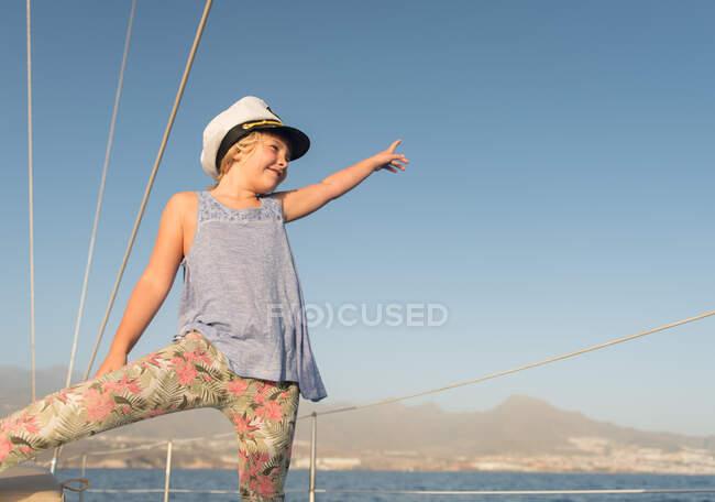 Positives Mädchen mit Kapitänsmütze sitzt an Deck eines teuren Bootes, das an sonnigen Tagen auf dem Wasser schwimmt — Stockfoto
