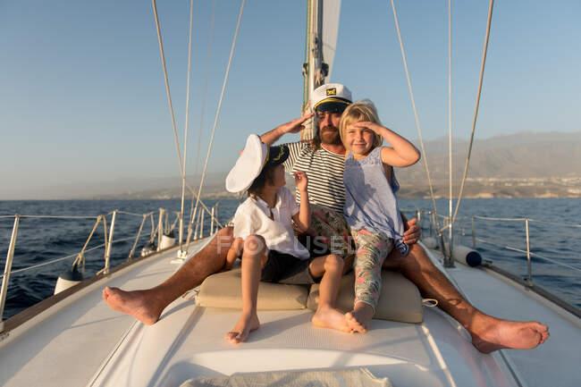 Позитивный отец, обнимающий счастливых детей в капитанских шляпах и сидящий на палубе дорогой лодки, плывущей по воде в солнечный день — стоковое фото