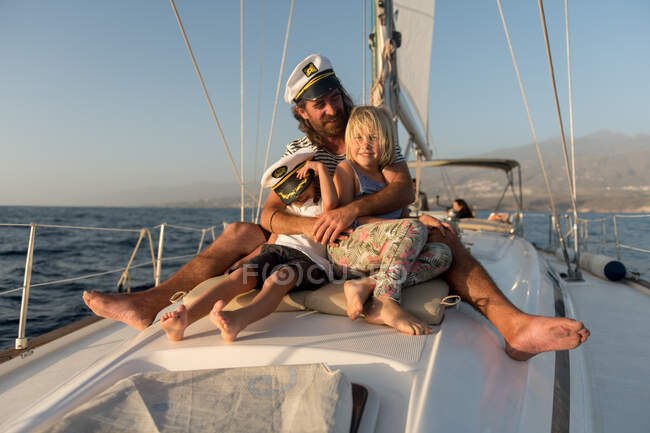 Positive father embracing happy kids in captain hats and sitting on deck of expensive boat floating on water in sunny day — Stock Photo