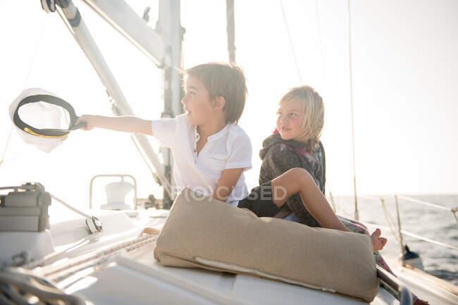 Bambini positivi seduti sul ponte laterale di barca costosa galleggiante sull'acqua nella giornata di sole — Foto stock