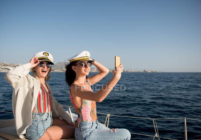 Вид сбоку красивых молодых женщин в солнцезащитных очках и капитанских люках, делающих селфи на мобильный телефон и сидящих на боковой палубе дорогой лодки, плывущей по воде в солнечный день — стоковое фото