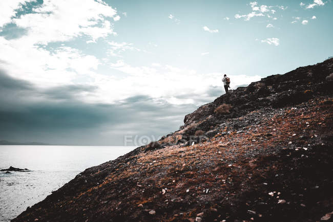 Silhouette of tourist standing on high mountain near sea and cloudy sky in Lanzarote, Canary Islands, Spain — Stock Photo