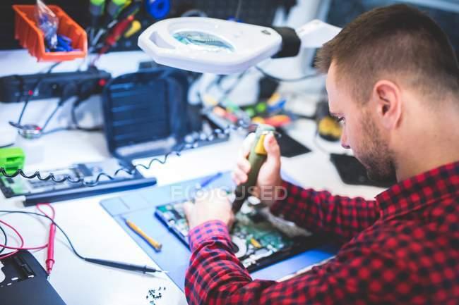 Mann repariert Laptop am Arbeitsplatz — Stockfoto