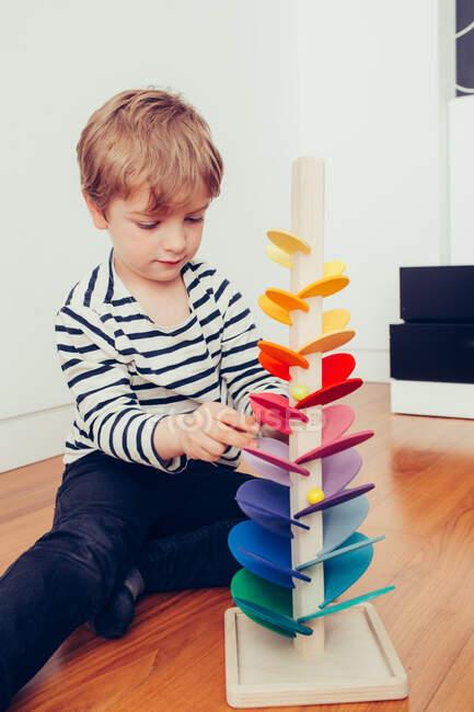 Rubia lindo chico jugando con waldorf sonando torre con canicas - foto de stock