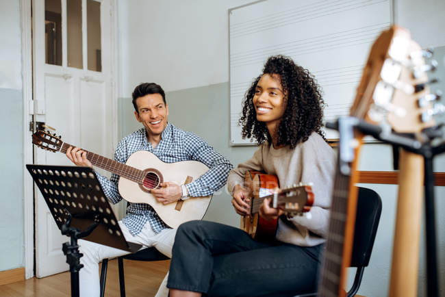 Junge Männer und Frauen beim Gitarrespielen während der Probe im Tonstudio. — Stockfoto