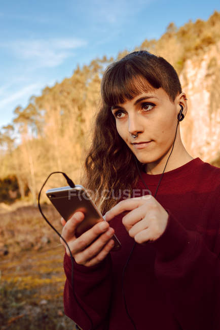 Young woman with piercing and earphones listening music on mobile phone in countryside — Stock Photo
