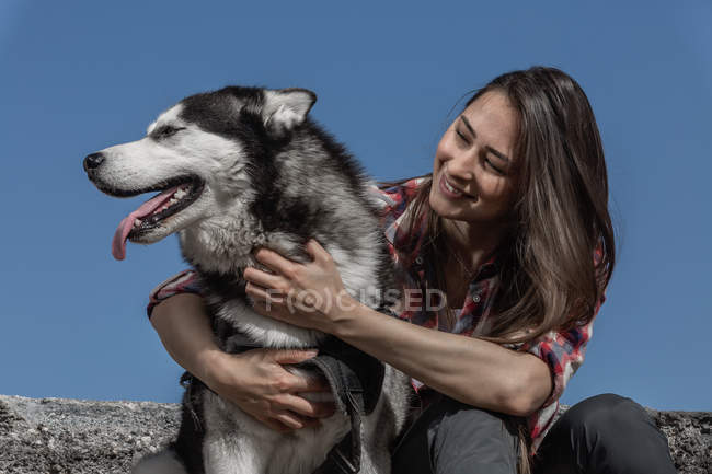 Cheerful young woman sitting near husky on rock in front of blue sky — Stock Photo