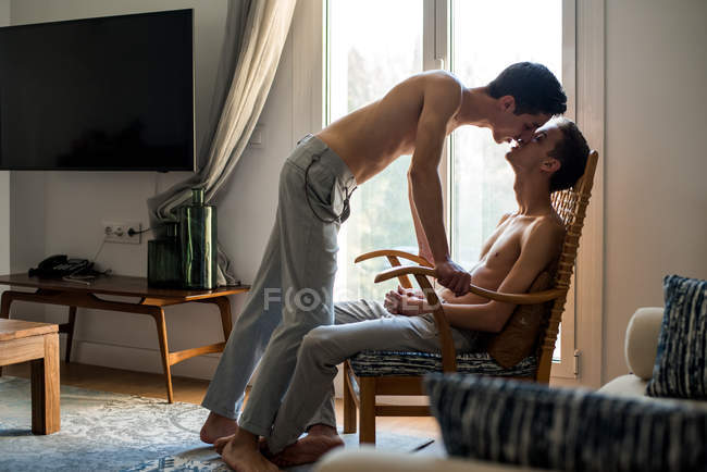 Stylish shirtless gay couple posing while sitting in a chair — Stock Photo